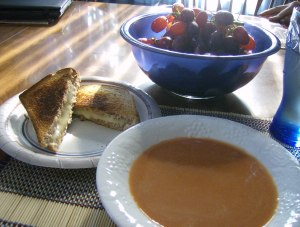 Creamy tomato soup and toasted cheese with red grapes